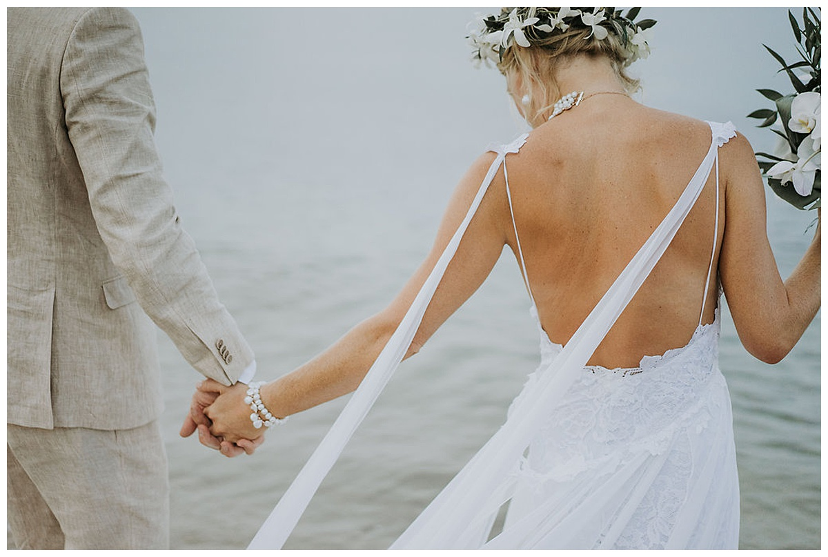 bride wearing a backless scrappy wedding dress with groom by the sea