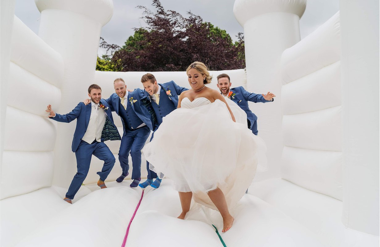 bride and groomsmen bouncing on a white bouncy castle